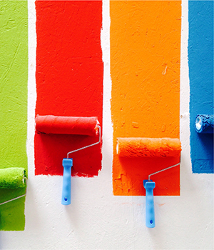 Colorful paint is rolled on a wall